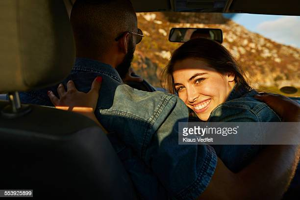 Woman hugging boyfriend while driving car