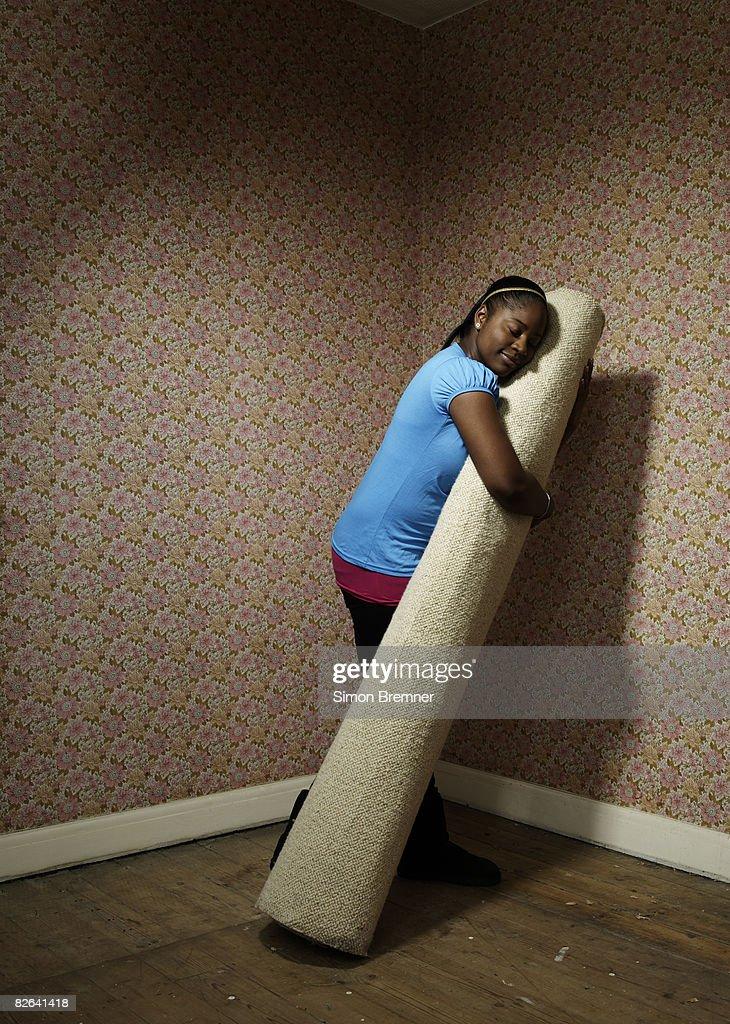 Woman hugging carpet : Stock Photo