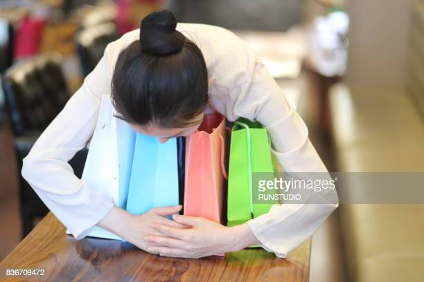 woman hugging colorful shopping bags in a cafe