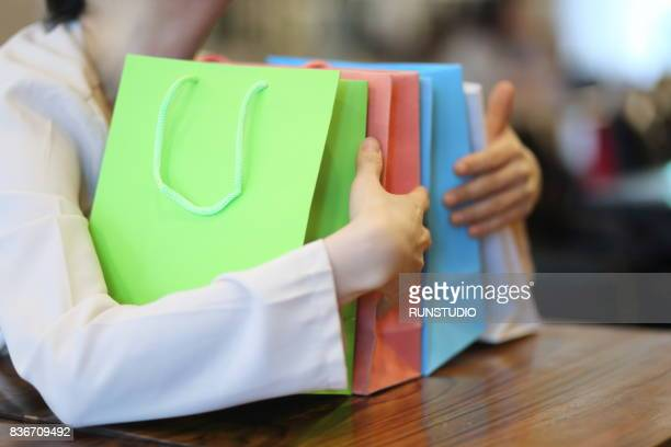 woman hugging colorful shopping bags - greed stock pictures, royalty-free photos & images