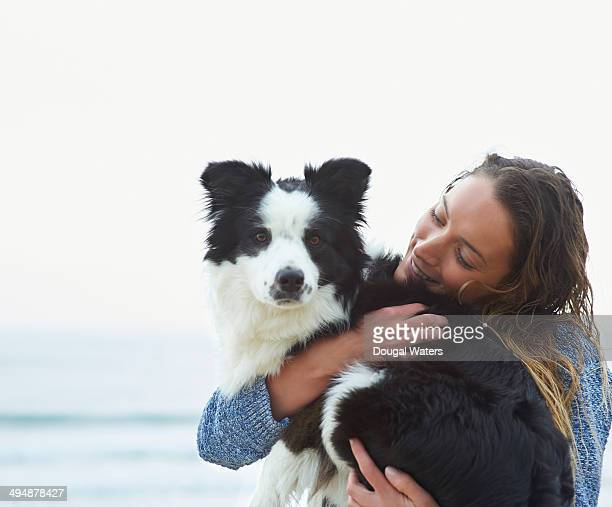 Woman hugging dog beside sea.