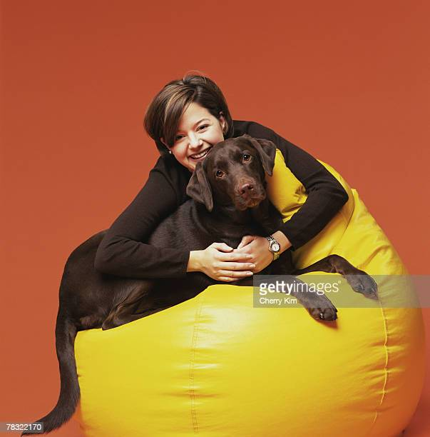 Woman hugging dog on bean bag chair