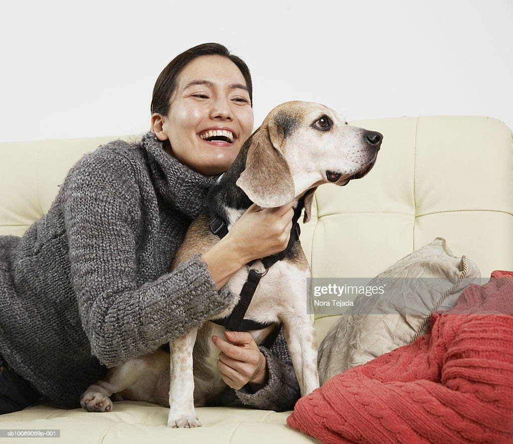 Woman hugging dog on sofa : Stockfoto