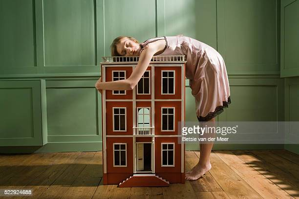 woman hugging doll house - dollhouse stock pictures, royalty-free photos & images