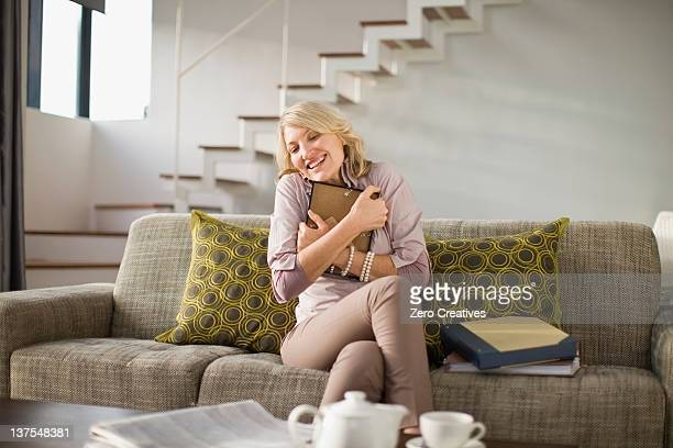 Woman hugging framed photo on couch