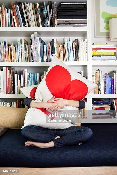 woman hugging heat pillows - cushion stock pictures, royalty-free photos & images