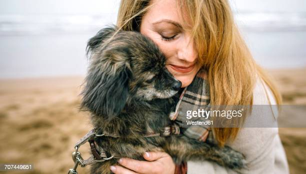 Woman hugging her dog on the beach in winter