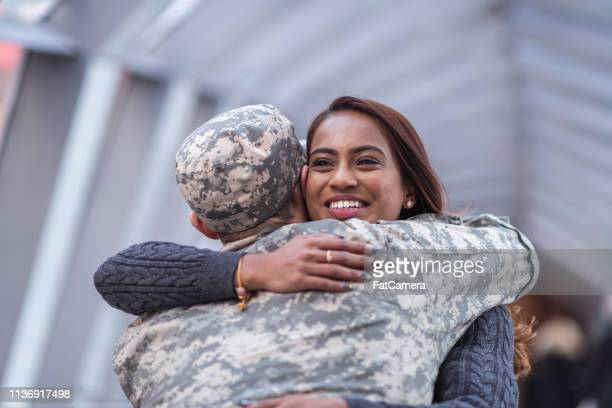 woman hugging her partner after returning home from service - military spouse stock pictures, royalty-free photos & images