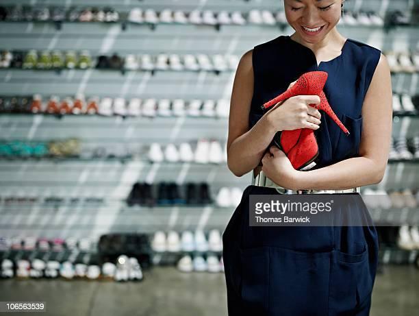 Woman hugging high heels in retail store