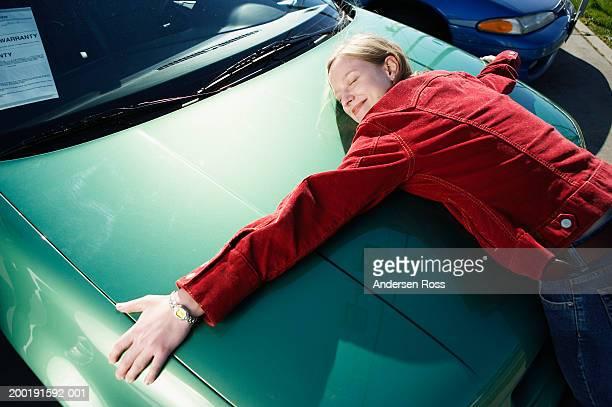 woman hugging hood of car, elevated view - umarmen stock-fotos und bilder