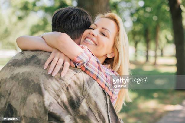woman hugging husband returning from the army service - civilian stock pictures, royalty-free photos & images