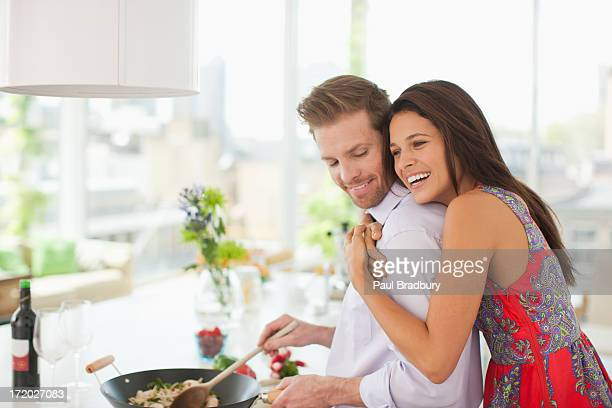 woman hugging husband while he's cooking in kitchen - women of penthouse stock photos and pictures