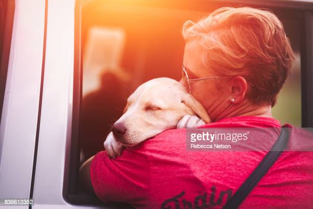 woman hugging labrador retriever puppy