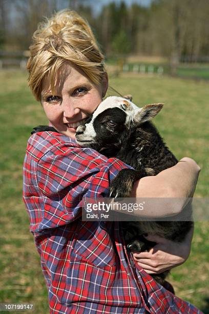 Woman hugging lamb in farm