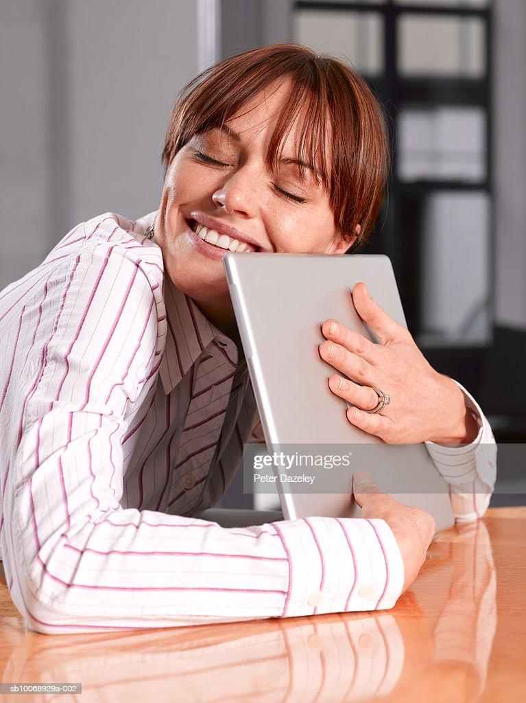 Woman hugging laptop, close-up : Stock Photo