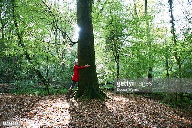 Woman hugging large tree in forest.