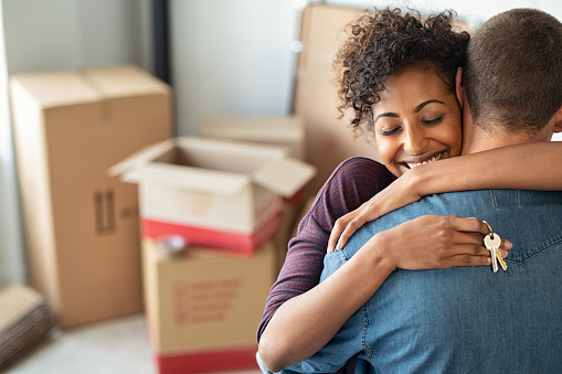 Woman hugging man and holding home keys 1158246435