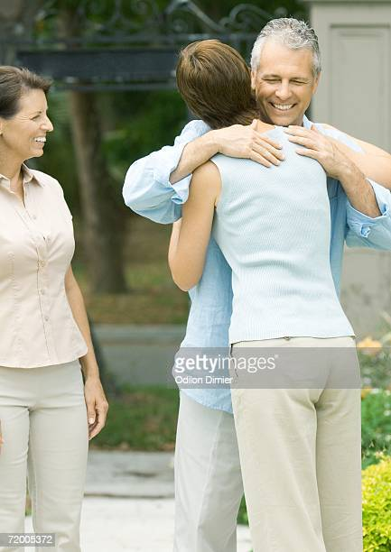 Woman hugging man as second woman watches smiling