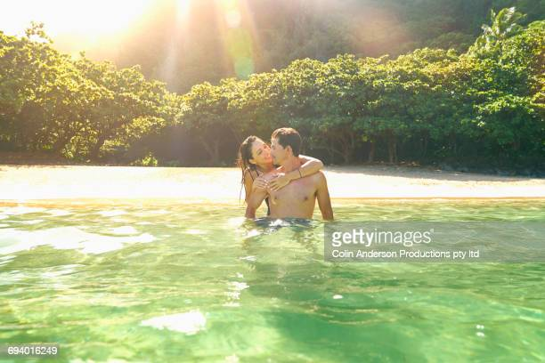 Woman hugging man in ocean