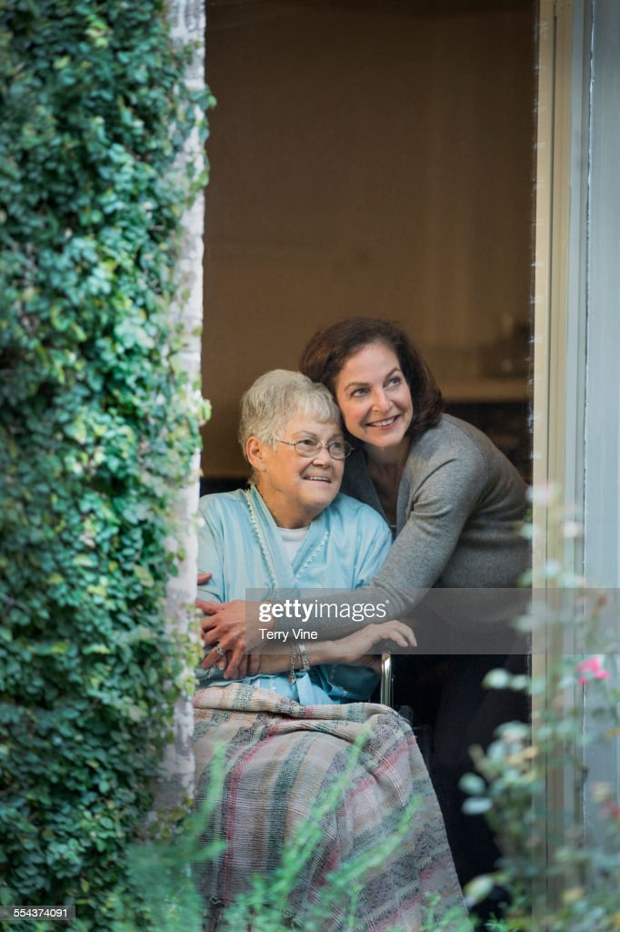 Woman hugging mother in wheelchair near window : Stock Photo