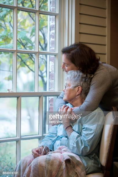 Woman hugging mother in wheelchair near window