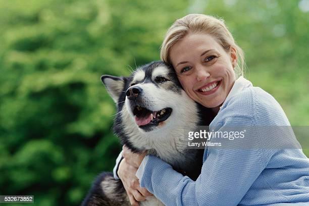 woman hugging pet dog - マラミュート犬 ストックフォトと画像