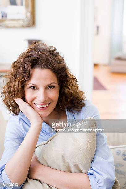 woman hugging pillow sitting on a couch - une seule femme d'âge moyen photos et images de collection