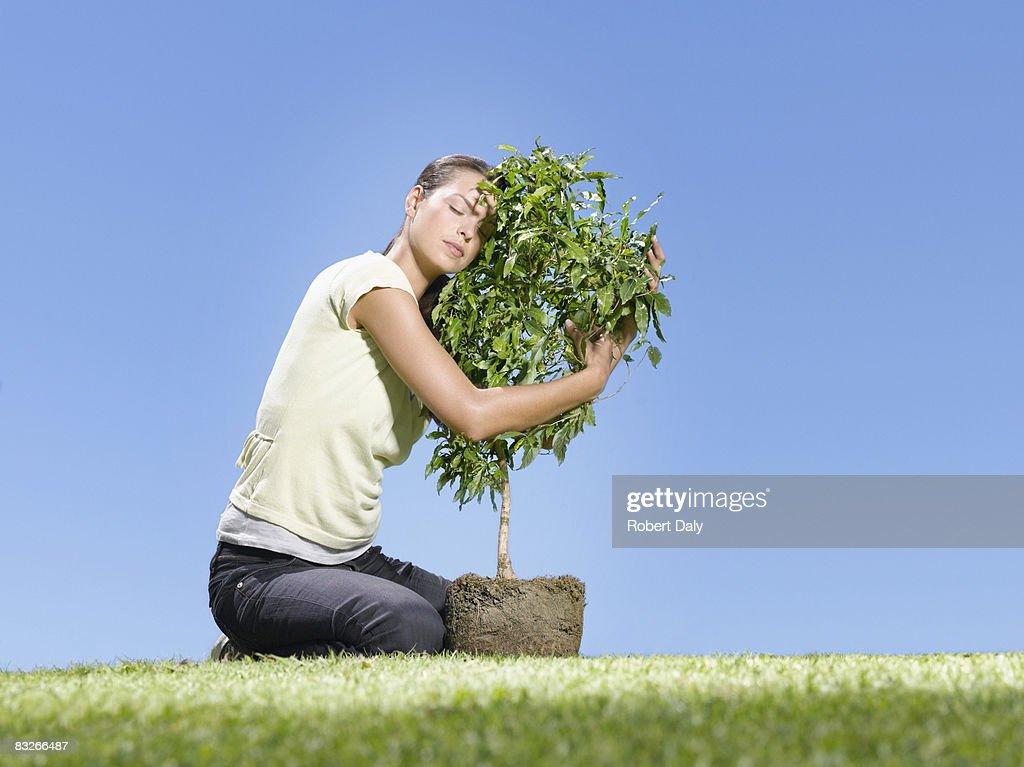 Woman hugging small tree : Stock Photo