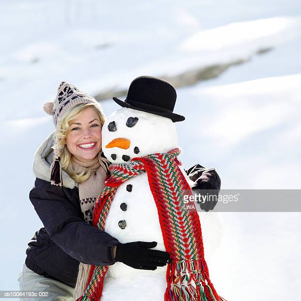 Woman hugging snowman, smiling, portrait