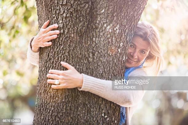 Woman hugging tree looking at camera smiling