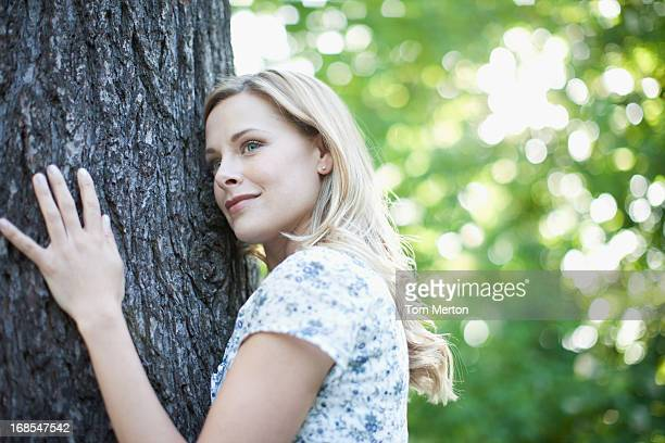 woman hugging tree outdoors - tree hugging stock pictures, royalty-free photos & images