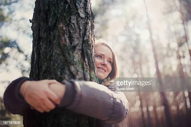 Woman  hugging tree, smiling.