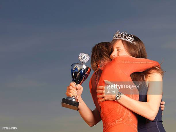 Woman hugging woman, holding trophy