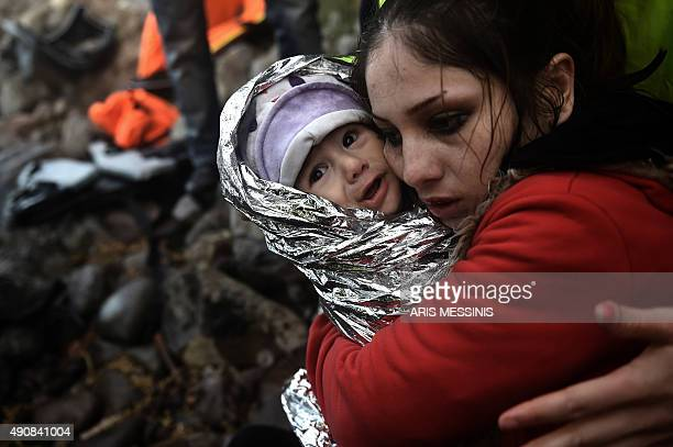 Woman hugs a baby wrapped in an emergency blanket as refugees and migrants arrive on the Greek island of Lesbos after crossing the Aegean sea from...
