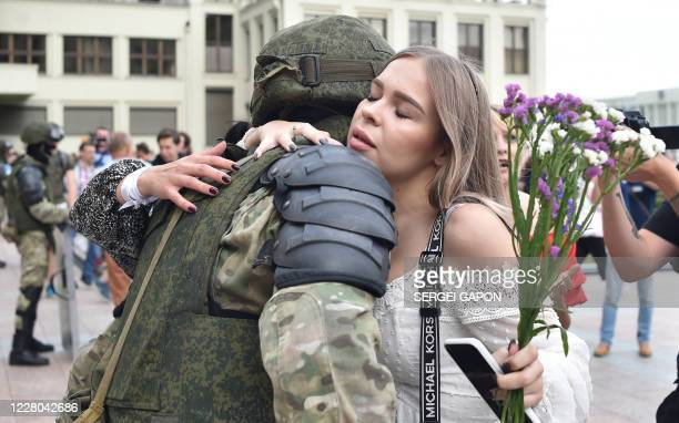 TOPSHOT A woman hugs a Belarus' law enforcement officer during a protest rally against police violence during recent rallies of opposition supporters...