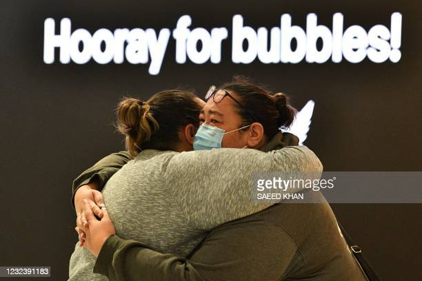 Woman hugs a family member before his departure for New Zealand at Sydney International Airport on April 19 as Australia and New Zealand opened a...