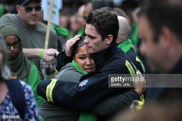 TOPSHOT A woman hugs a firefighter as members of the public take part in a silent march as part of commemorations on the first anniversary of the...
