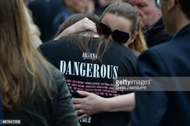 TOPSHOT A woman hugs a girl wearing a tshirt from Ariana Grande's Dangerous Woman near floral tributes in Albert Square in Manchester northwest...