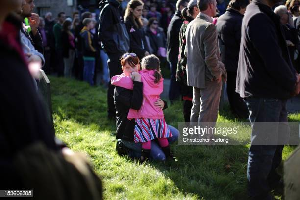 A woman hugs a young child as members of the community of Machynlleth stand in the church yard of St Peter's Church for a service with prayers for...