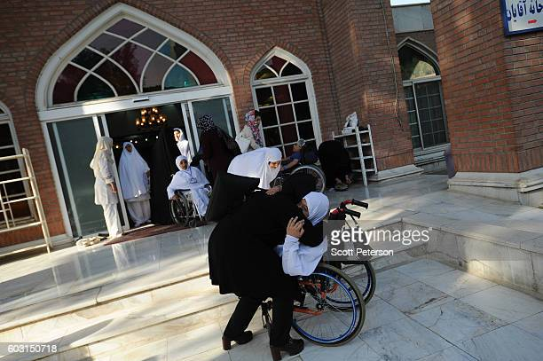 A woman hugs her daughter as wheelchairbound Iranians prepare to reenact some parts of the Hajj pilgrimage as Iranians marked the Eid AlAdha Islamic...