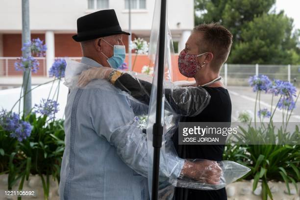 A woman hugs her father through a plastic curtain to protect him from possible coronavirus infection after visits were allowed at the Ballesol...