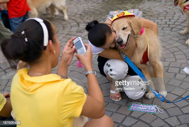 A woman hugs her golden retriever while a friend takes a photo at a dog show held in Benjasiri Park in Bangkok