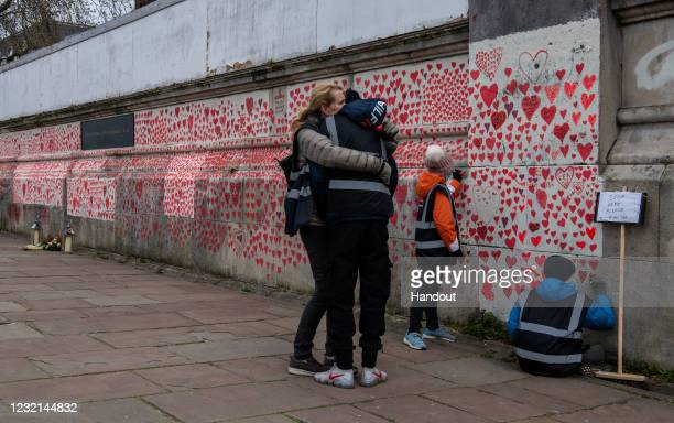 Woman hugs her son as they draw hearts on the Covid-19 Memorial Wall which is nearing completion opposite Parliament on April 6 in London, England....