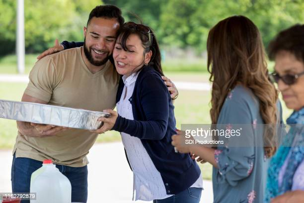 woman hugs son-in-law during family picnic - zia e nipote foto e immagini stock
