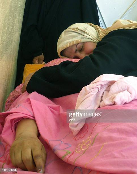 A woman hugs the covered body of a female relative at the hospital in the northeastern town of Baquba 60 kms from Baghdad on August 31 2009 The woman...
