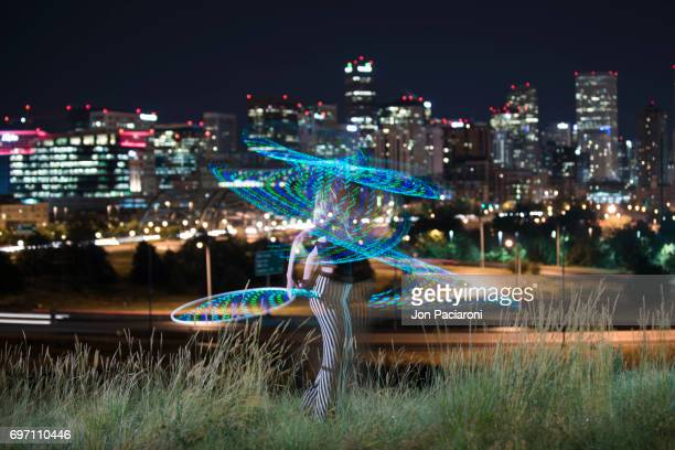 Woman hula hooping with an illuminated plastic hoop at night.