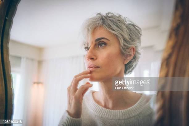 Gray haired woman by the mirror