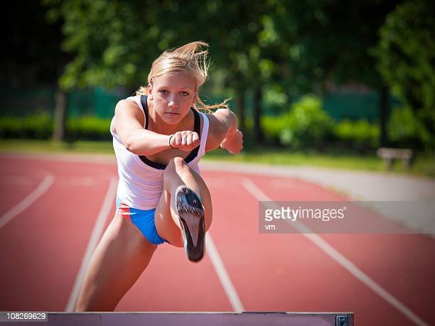 woman hurdling - hurdle stock photos and pictures