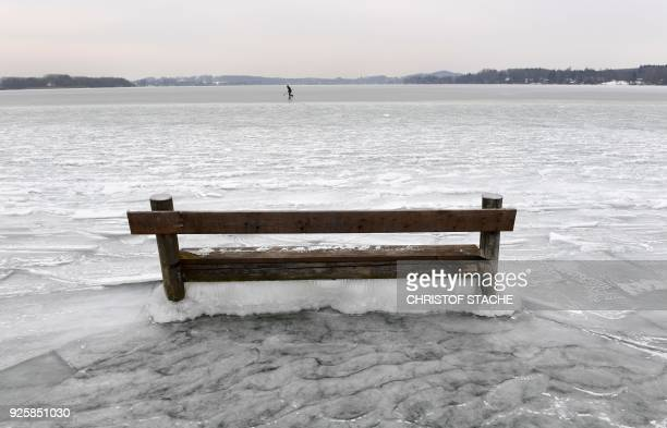TOPSHOT A woman ice skates behind a bench caught in the ice on the frozen Woerthsee lake on March 1 2018 near the Bavarian village of Inning southern...