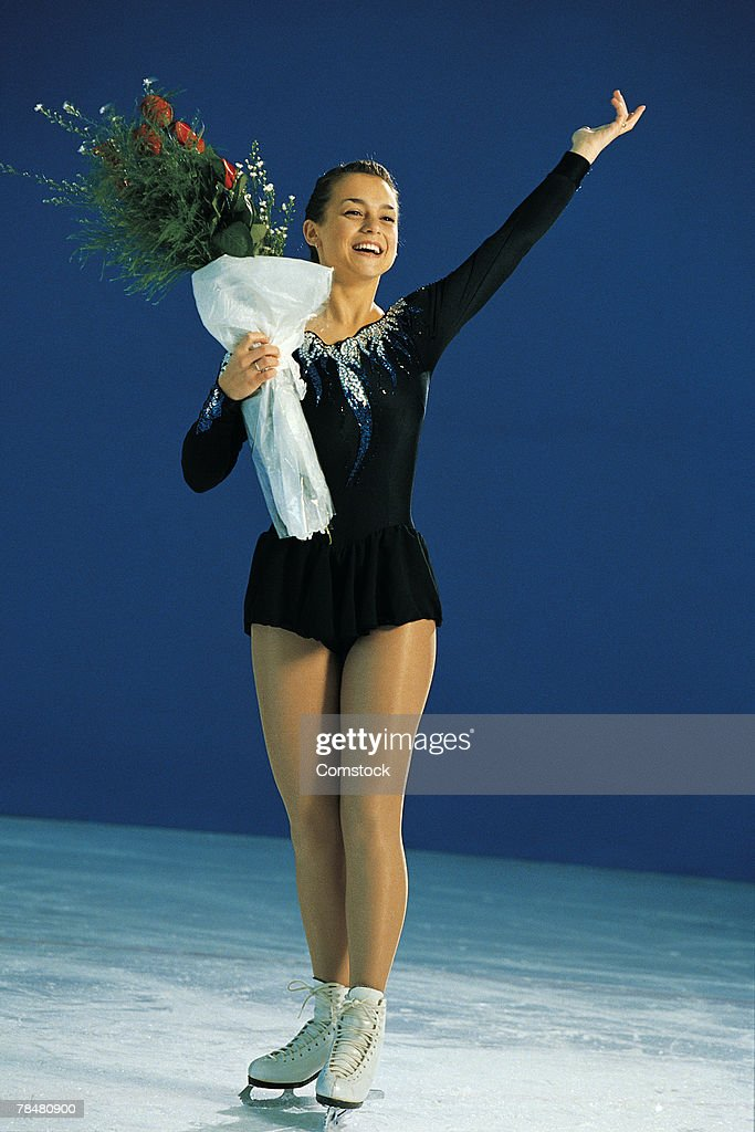 Woman ice skating , holding bouquet of flowers : Stock Photo